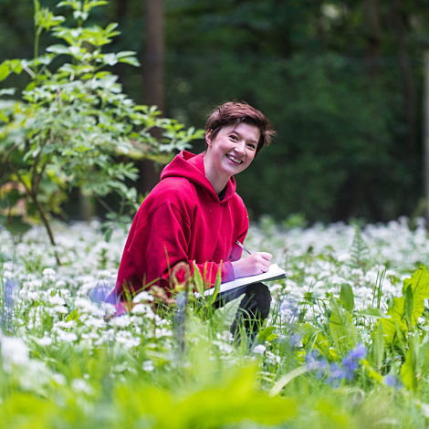 female student smiling in the outdoors with a notepad